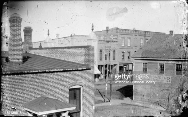 Elevated view of First and Main Streets Black River Falls Wisconsin 1891 A banner promoting the 1891 Wisconsin State Fair is posted on the side of a...