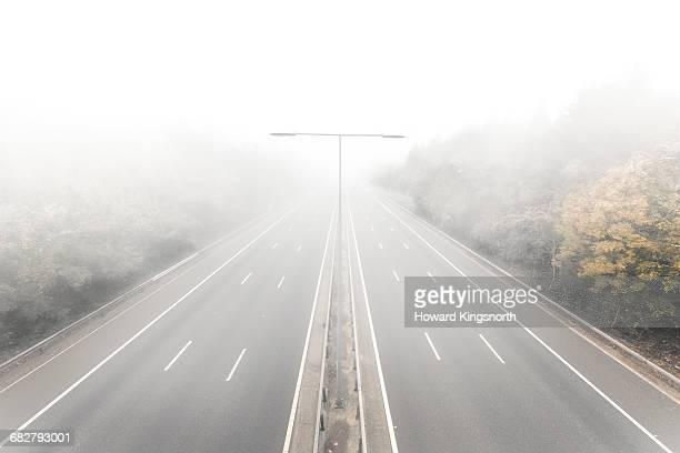 elevated view of foggy road - fog stock pictures, royalty-free photos & images