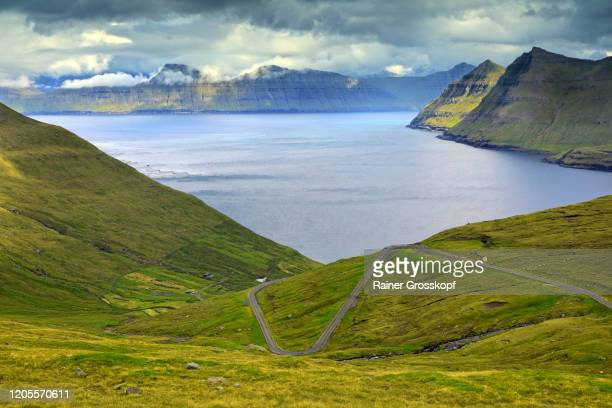 elevated view of grassy mountains surrounding a bay with a road leading down into the valley to the sea - rainer grosskopf stock-fotos und bilder