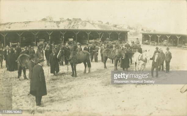 Elevated view of group of people and horses in front of horse sheds for farmers after the 1911 flood looking north downtown on Harrison Street Black...