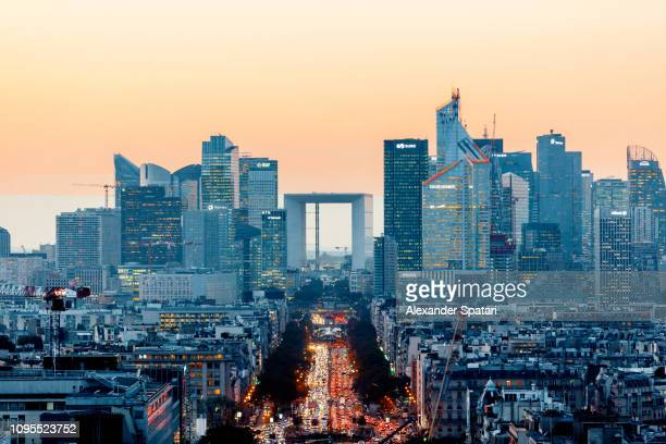 elevated view of illuminated skyscrapers at la defense financial district and avenue des champs-elysees at dusk, paris, france - skyline photos et images de collection