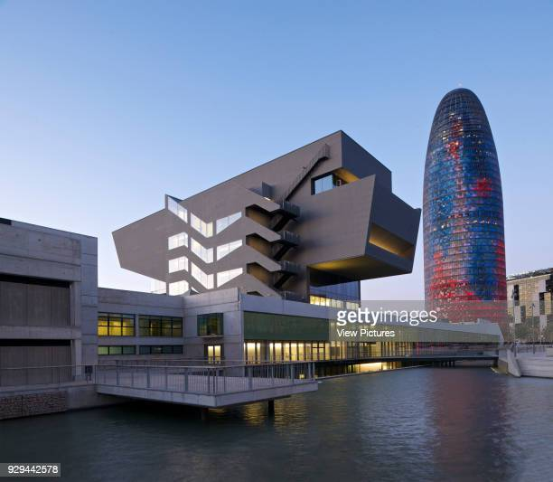Elevated view of lake, museum and Agbar Tower at dusk. Museu del Disseny de Barcelona, Barcelona, Spain. Architect: MBM Arquitectes, 2013.