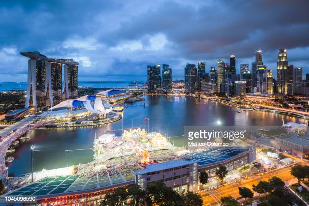 elevated view of marina bay at dusk, singapore - marina bay sands stock photos and pictures