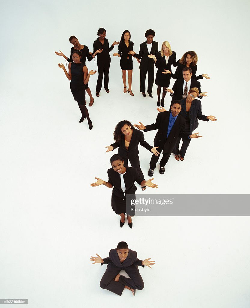 Elevated view of men and women standing to form a question mark : Stock Photo