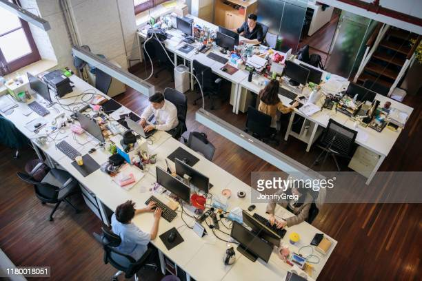 elevated view of open plan business office in shanghai - small group of people stock pictures, royalty-free photos & images