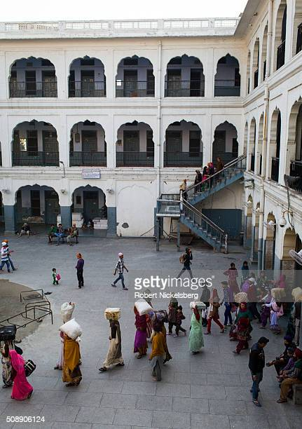 Elevated view of people a number with belongings help on their heads in a courtyard outside a public guesthouse Amritsar India February 23 2014 The...