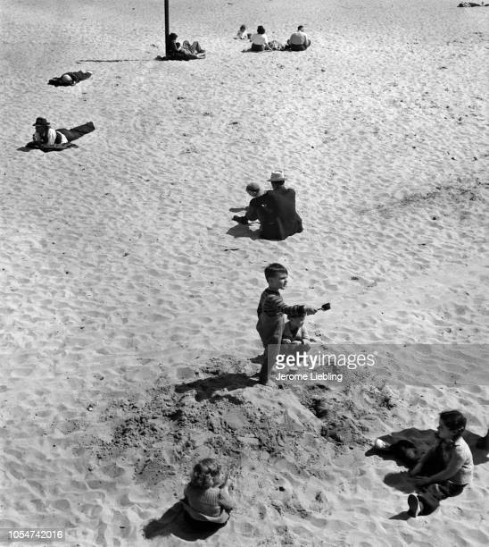 Elevated view of people as they sit on the sand at Coney Island Beach Brooklyn New York New York 1947