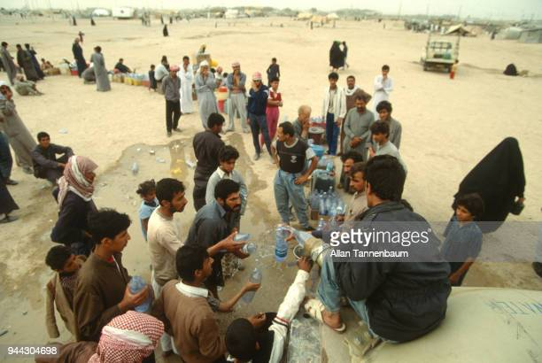 Elevated view of refugees as they fill plastic bottles with water from a hose during the Gulf War Iraq 1991 Others wait to fill other containers