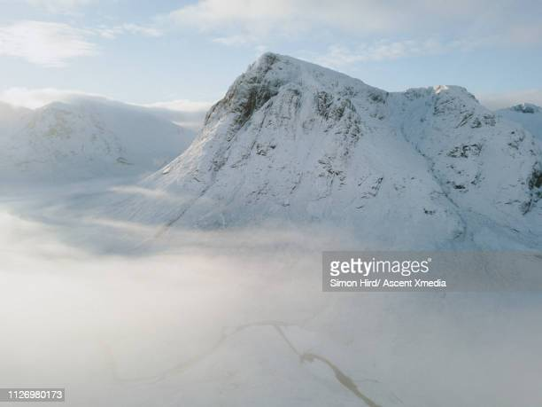 elevated view of river winding through snowscape below mountain peak - winter stock pictures, royalty-free photos & images