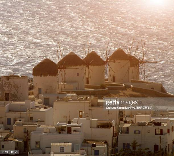 Elevated view of rooftops and traditional windmills on coast, Mykonos, Cyclades, Greece