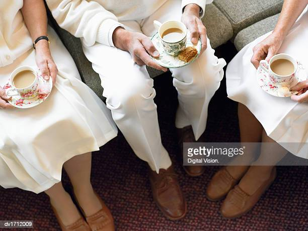 Elevated View of Senior Men and Women Sitting Wearing Bowling Sportswear Holding Cups of Tea