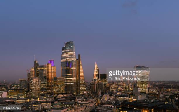 elevated view of the city of london's illuminated financial district skyline at dusk - tim grist stock pictures, royalty-free photos & images