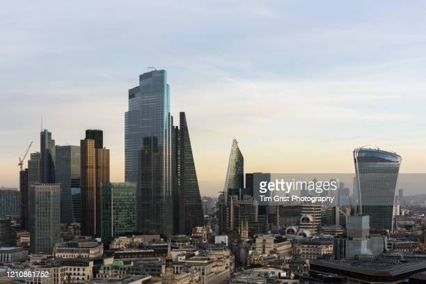 elevated view of the city of london's illuminated financial district skyline - tim grist stock pictures, royalty-free photos & images
