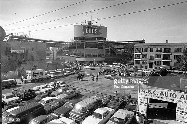 Elevated view of the exterior facade of Wrigley Field and the surrounding parking lots as Chicago Cubs baseball fans walk towards entrance during a...