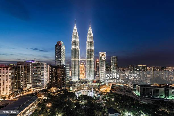 elevated view of the petronas towers at dusk - petronas towers stock pictures, royalty-free photos & images