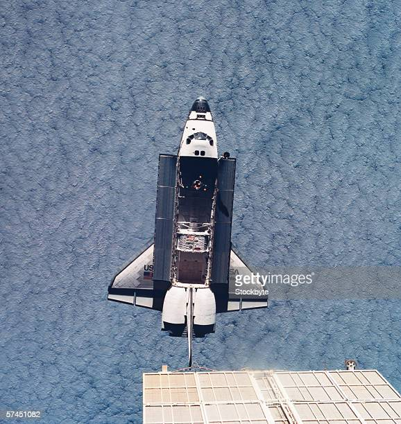 Elevated view of the space shuttle orbiting above earth with its cargo bay open