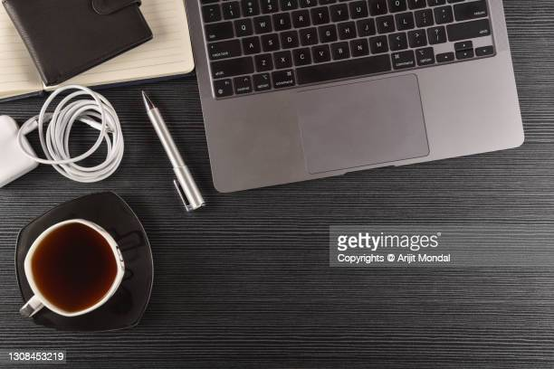 elevated view of wooden office work table with laptop, laptop charger, wallet, diary, pen, coffee cup - multimedia stock pictures, royalty-free photos & images