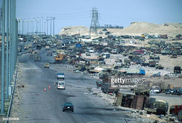 Elevated view of wrecked vehicles that line a road beside a US military checkpoint on a highway during the Gulf War Iraq 1991 At center a US solider...