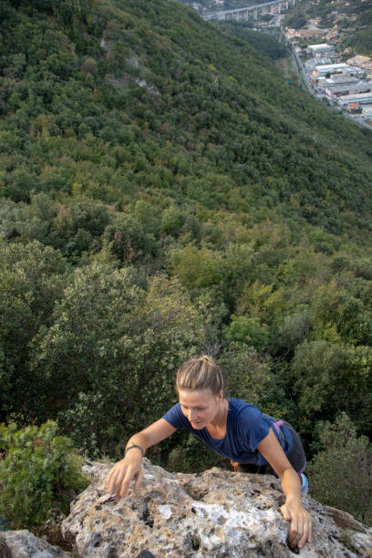 Elevated view of young woman climber reaching top of steep rock wall