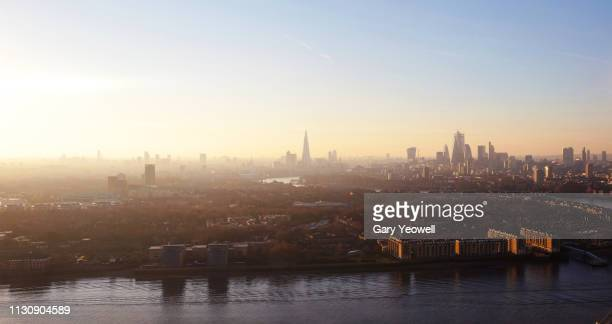 elevated view over london city skyline at sunset - isle of dogs london stock pictures, royalty-free photos & images