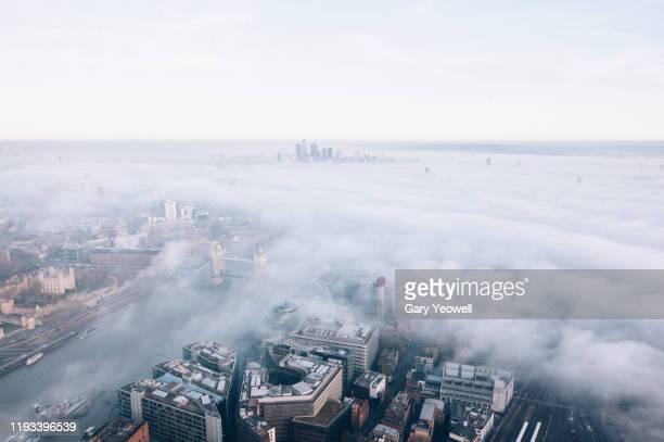 elevated view over london city skyline in fog - theems stockfoto's en -beelden