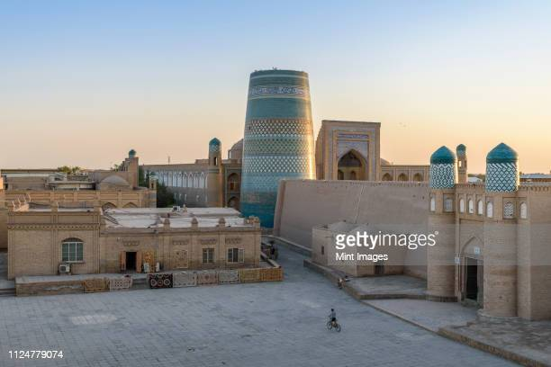 elevated view over the courtyard of historic monuments with kalta minor minaret in the centre of khiva, uzbekistan. - oezbekistan stockfoto's en -beelden