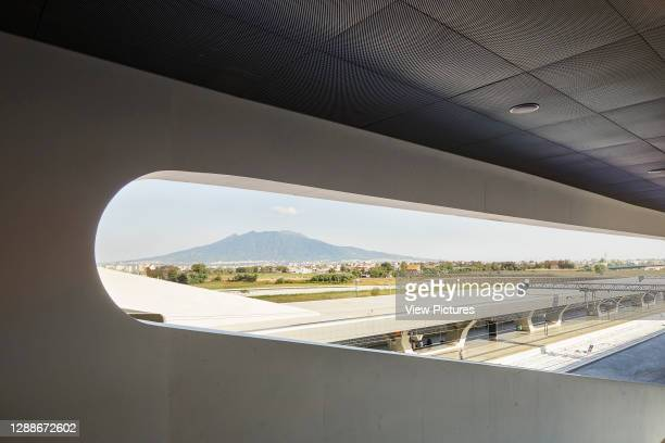 Elevated view through structural void with platform and Mount Vesuvius in distance. Afragola Train Station Naples, Naples, Italy. Architect: Zaha...
