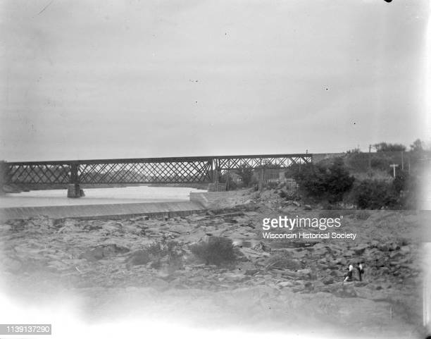 Elevated view upriver towards a bridge and dam Black River Falls Wisconsin 1892 Two people are walking among the rocks on the lower right Identified...