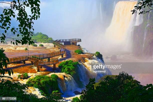 印象的なイグアスに高架木道歩道橋の滝の風景、自然風景 - 牧歌的な悪魔の喉笛 - ブラジルのフォスの国境で劇的な美しさはパラグアイの南米ミシオネス州、パラナ州、アルゼンチンのプエルト ・ イグアス イグアス - フォスドイグアス ストックフォトと画像