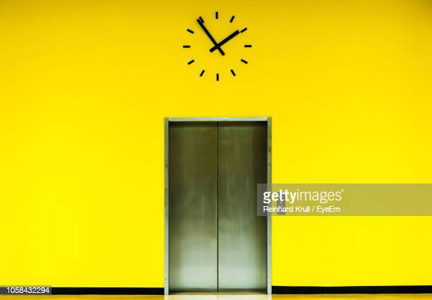 elevator below clock on yellow wall - time of day stock pictures, royalty-free photos & images