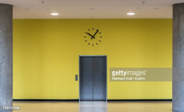 Elevator Below Clock On Yellow Wall