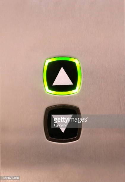 Elevator buttons on silver background, up button highlighted