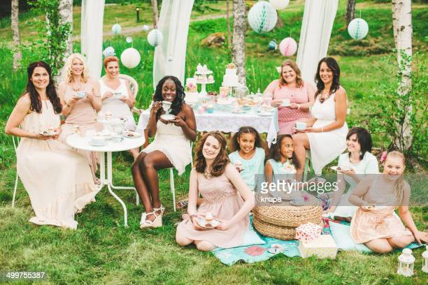 Eleven women having a garden party with dessert table