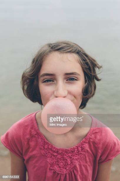 Eleven year old girl blowing bubble gum bubble