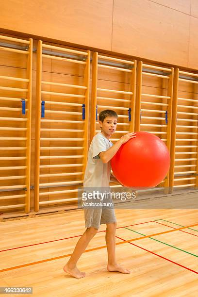 Eleven Years Old Boy Holding Red Exercise Ball, School Gymnasium