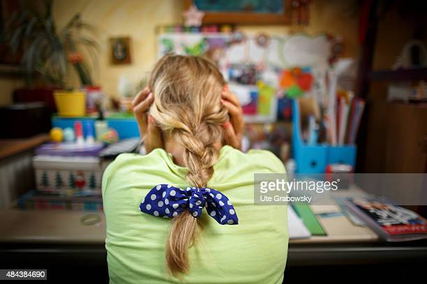 Eleven years old girl sitting at adesk doing her homework on August 10 2015 in Bonn Germany