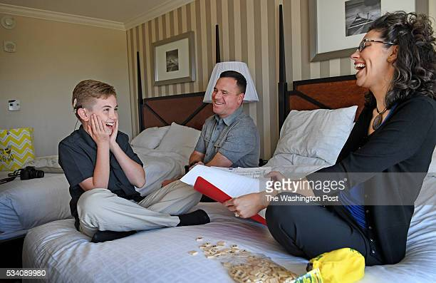 Elevenyearold Neil Maes who is a deaf contestant in the Scripps National Spelling Bee studies with his mother and father Peter and Christy Maes at...