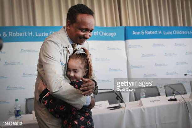 Elevenyearold Sofia Sanchez gives a hug to Dr Osama Eltayeb following a press conference which she attended with her heart surgery team to discuss...