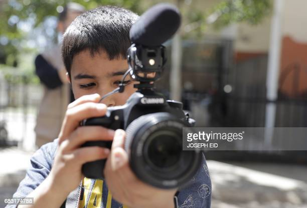Elevenyearold Syrian refugee Mostafa Abdallah from the Syrian town of Minbej films his friends who are acting in Beirut's southern suburb of Shatila...