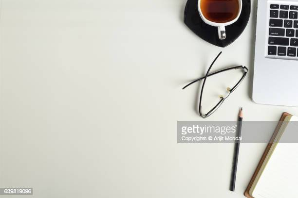 Eleveted View of Office Table with Laptop Keyboard, tea cup, notepad, pencil, Eye Glasses with White Background Copy Space