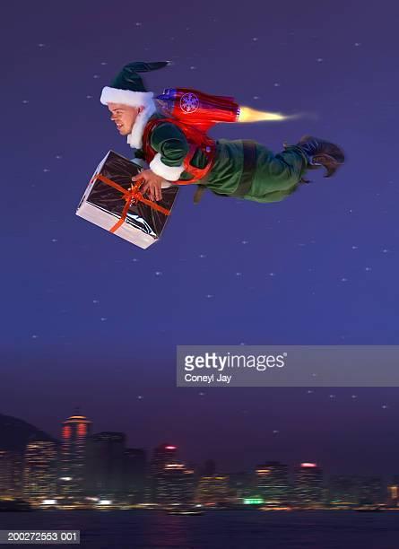 'elf' flying, 'jet pack' on back, holding present (digital composite) - dwarf man stock pictures, royalty-free photos & images