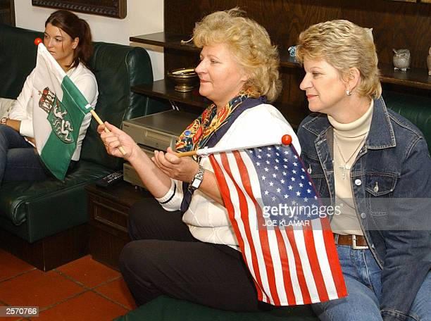Elfriede Kling and Gabriele Edlinger wave Styrian and US flags as they watch California's election's results along with the Mayor of Thal Peter Urdl...