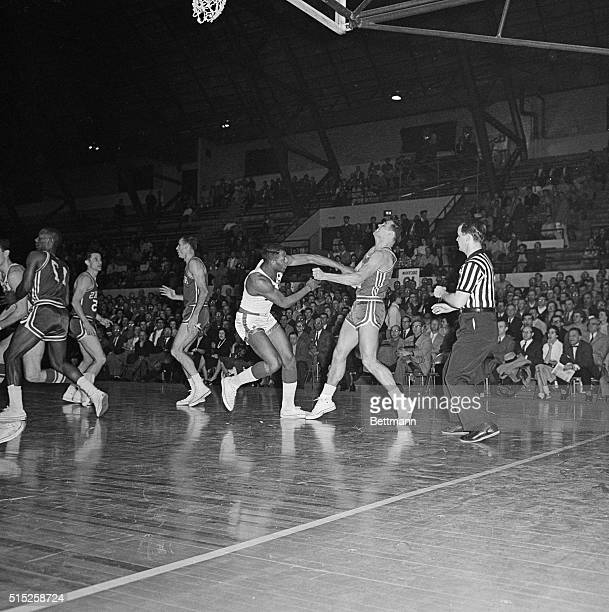 Elgin Baylor of the Minneapolis Lakers takes a poke at Cliff Hagen St Louis Hawks during the third game of the Western Division NBA playoffs here...