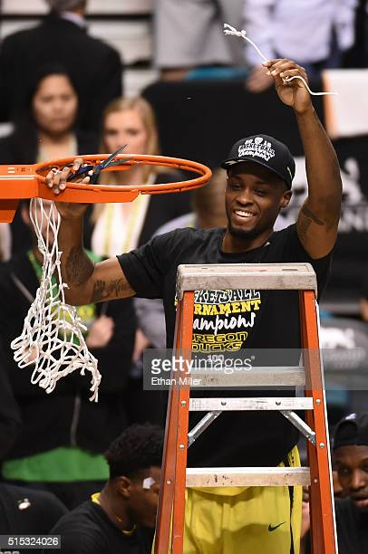 Elgin Cook of the Oregon Ducks cuts down a piece of a net as he celebrates the team's 8857 victory over the Utah Utes to win the championship game of...