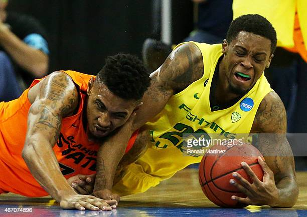 Elgin Cook of the Oregon Ducks recovers a loose ball against Le'Bryan Nash of the Oklahoma State Cowboys in the first half during the second round of...