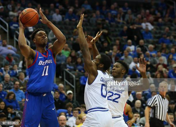 Eli Cain of the DePaul Blue Demons attempts a shot as Khadeen Carrington and Myles Cale of the Seton Hall Pirates defend during the first half of a...
