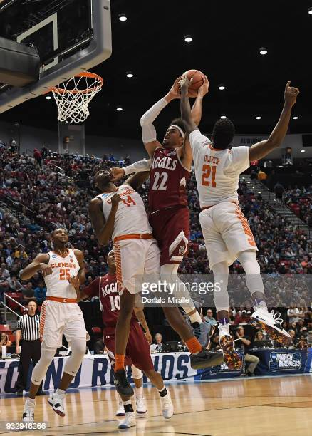 Eli Chuha of the New Mexico State Aggies shoots against Elijah Thomas and Anthony Oliver II of the Clemson Tigers in the first half in the first...