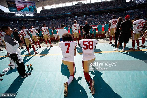 Eli Harold and Colin Kaepernick of the San Francisco 49ers kneel on the sideline during the anthem prior to the game against the Miami Dolphins at...