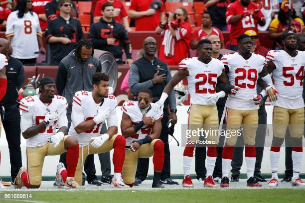 Eli Harold Arik Armstead and K'Waun Williams of the San Francisco 49ers kneel during the National Anthem before a game against the Washington...