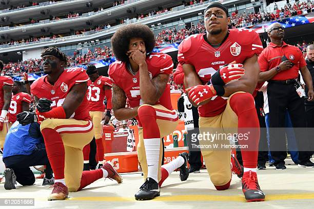 Eli Harold, Colin Kaepernick and Eric Reid of the San Francisco 49ers kneel on the sideline during the anthem prior to the game against the Dallas...